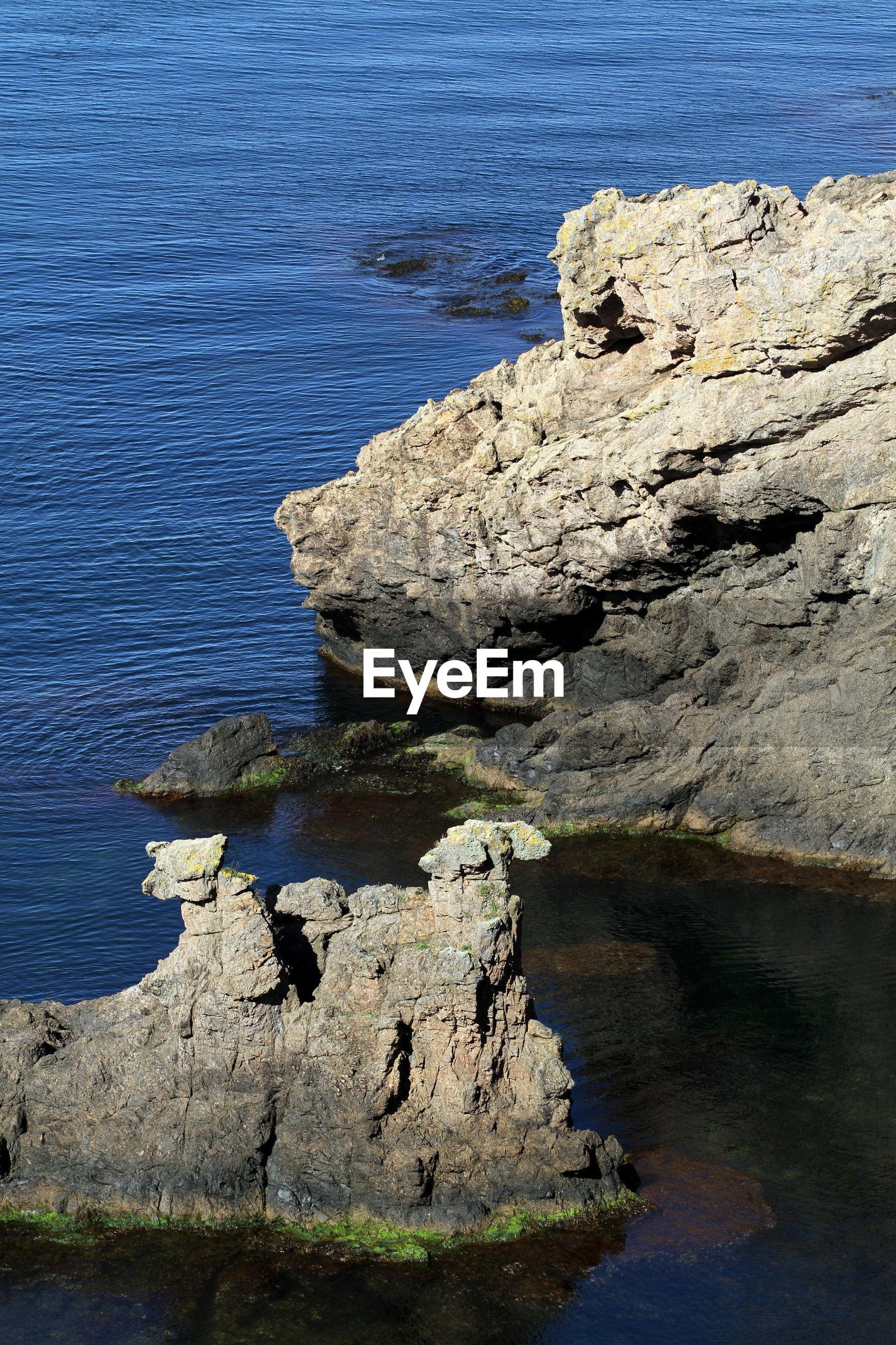 High angle view of rocks on sea shore