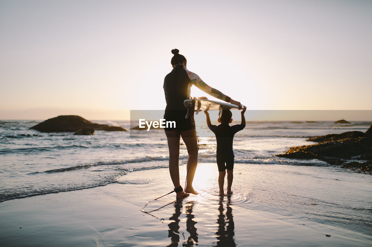sky, sea, sunset, water, beach, land, full length, real people, leisure activity, beauty in nature, standing, scenics - nature, lifestyles, silhouette, nature, two people, clear sky, men, women, horizon over water
