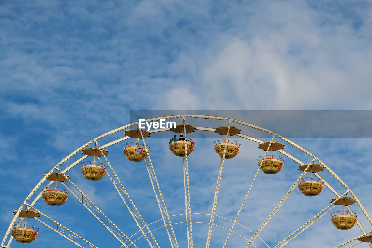 Low Angle View Of Ferris Wheel Against Blue Sky During Sunny Day