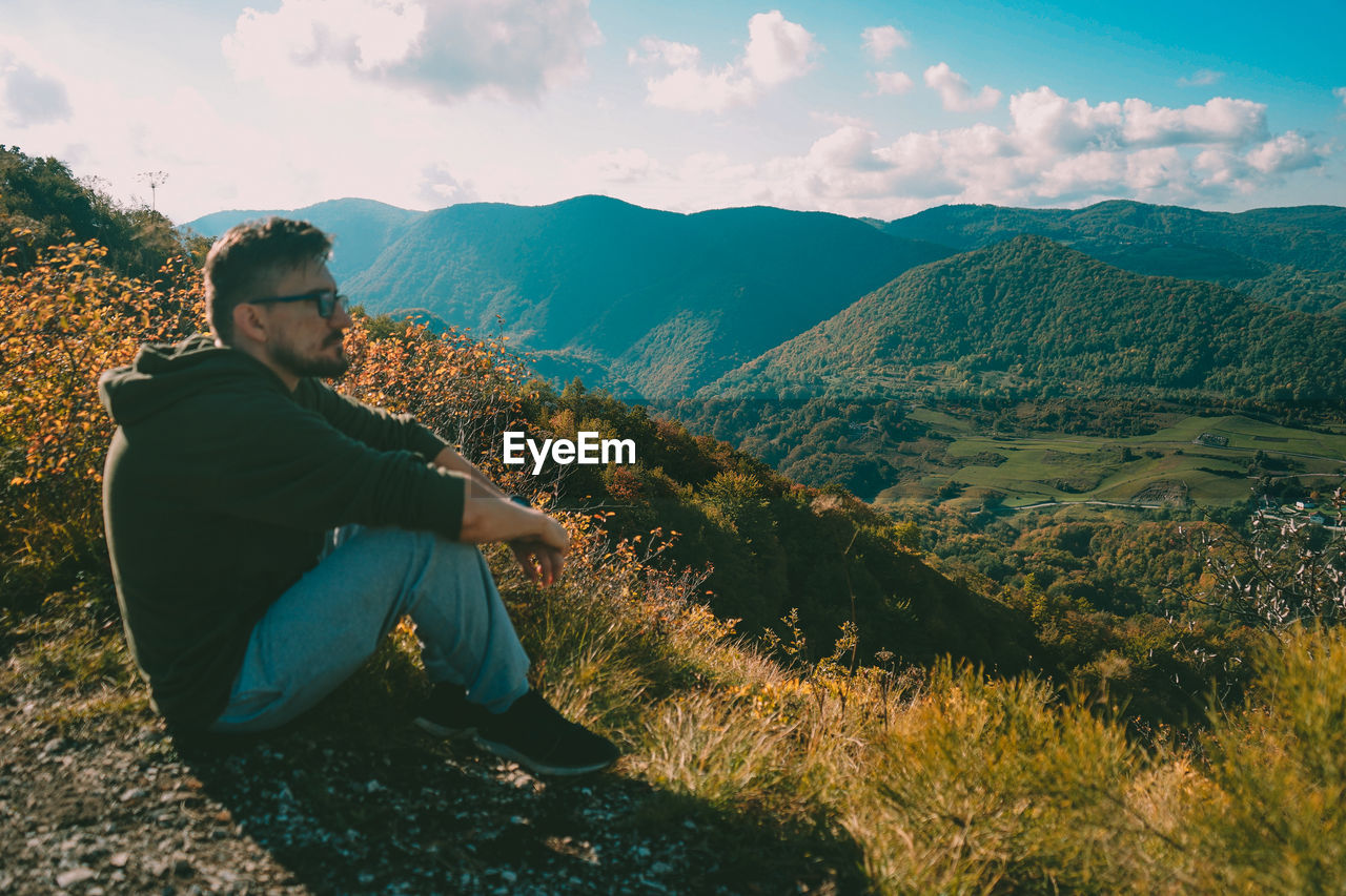 Young man sitting on mountain against sky