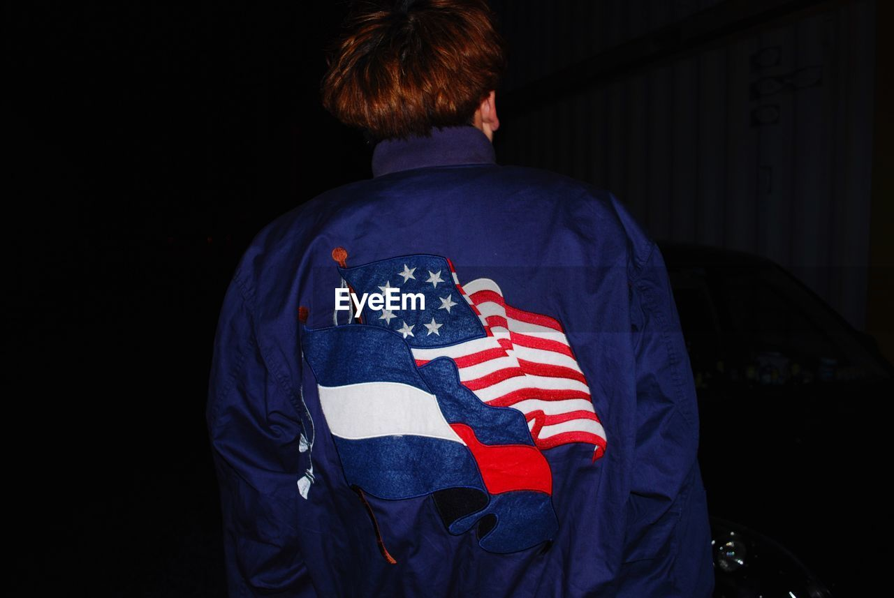 Rear View Of Man Wearing Jacket With American Flag Print Against Black Background