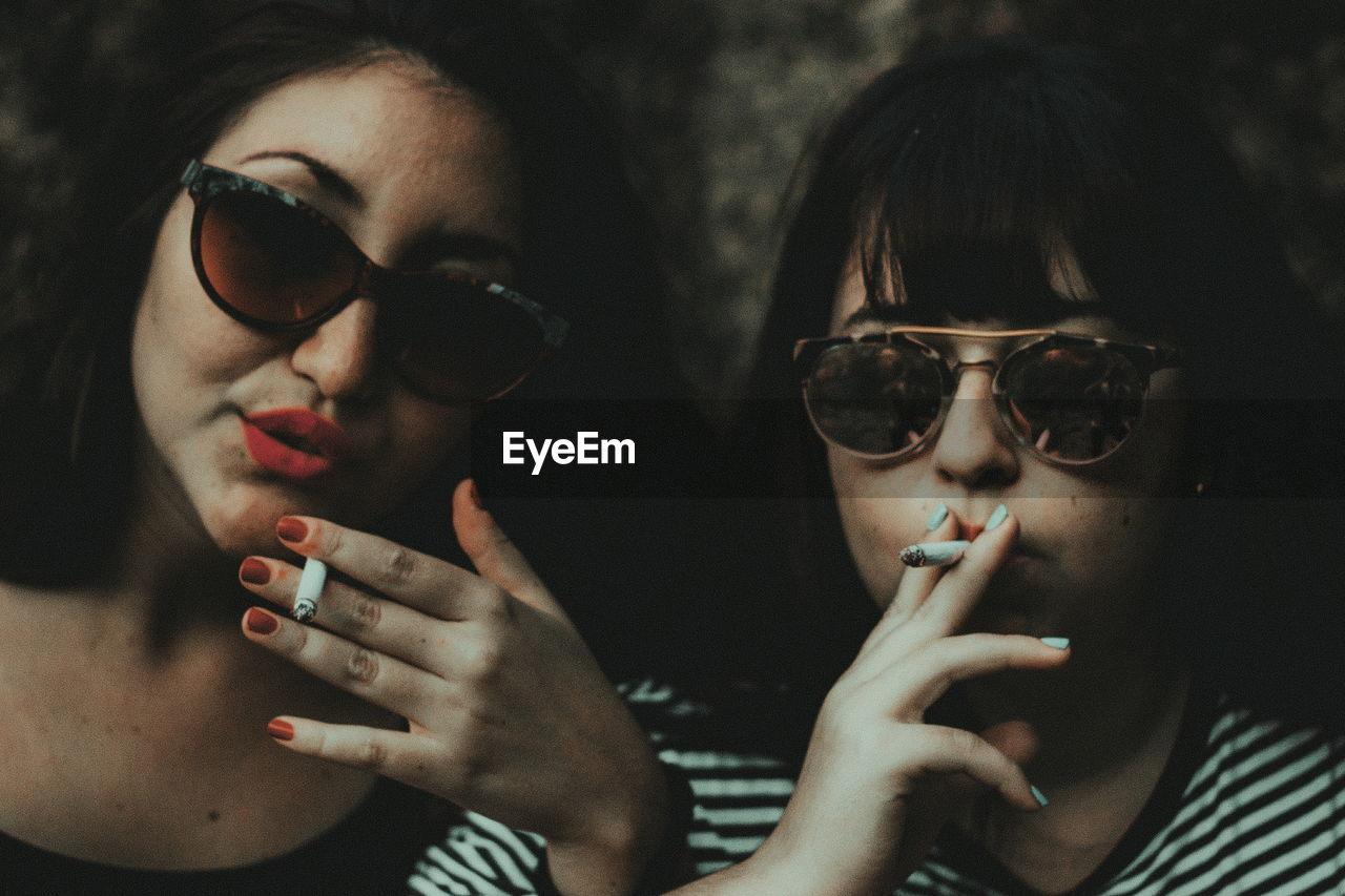 Close-Up Portrait Of Women Smoking Cigarette