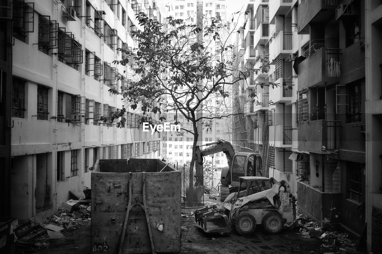 building exterior, architecture, built structure, building, mode of transportation, transportation, city, land vehicle, day, tree, construction industry, construction machinery, no people, construction site, outdoors, nature, motor vehicle, plant, car, earth mover, apartment