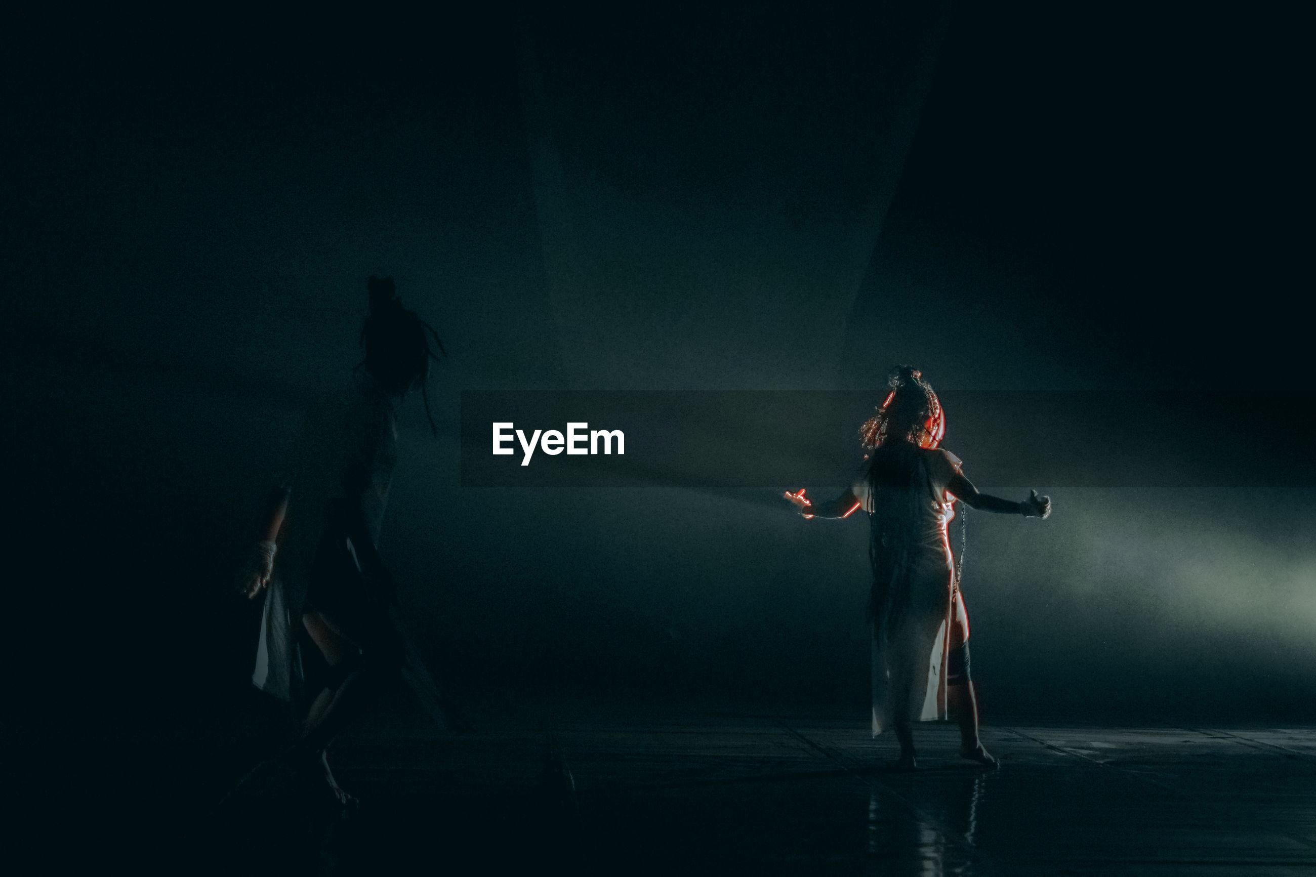 REAR VIEW OF PEOPLE DANCING IN NIGHTCLUB