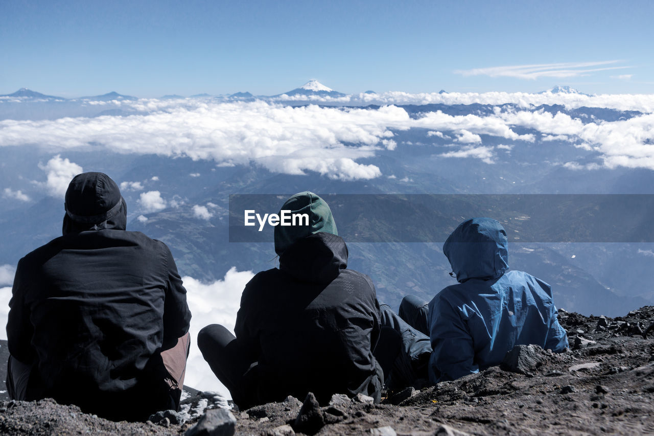 mountain, scenics - nature, leisure activity, beauty in nature, sky, lifestyles, adventure, rear view, winter, real people, nature, sitting, mountain range, people, hiking, cold temperature, men, tranquil scene, group of people, warm clothing, outdoors, looking at view, snowcapped mountain