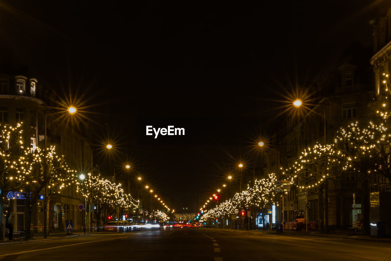illuminated, night, street, street light, city, lighting equipment, architecture, transportation, built structure, glowing, road, building exterior, no people, sky, motion, motor vehicle, the way forward, mode of transportation, land vehicle, light, outdoors, electricity