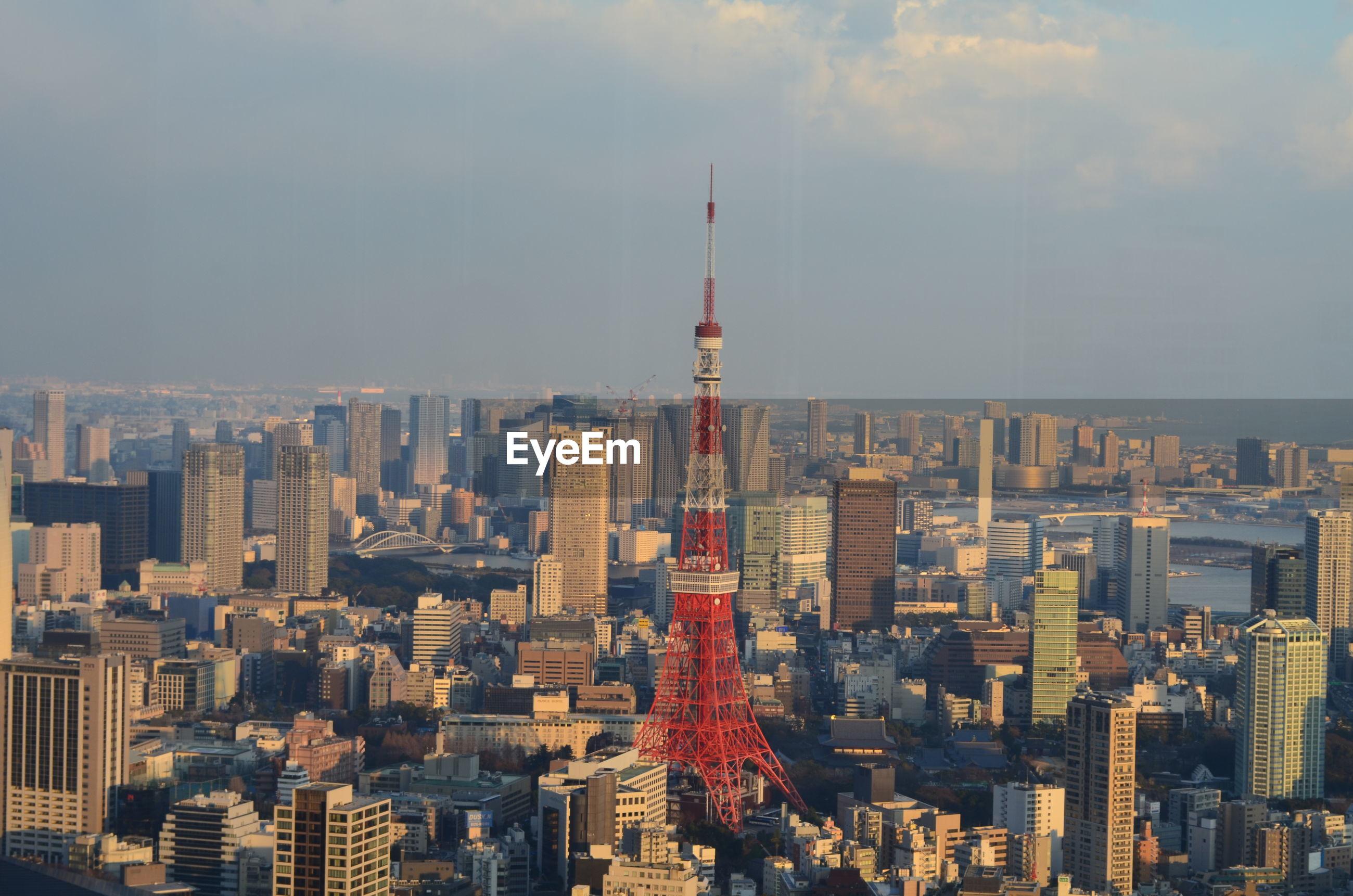 Tokyo tower amidst buildings against sky in city