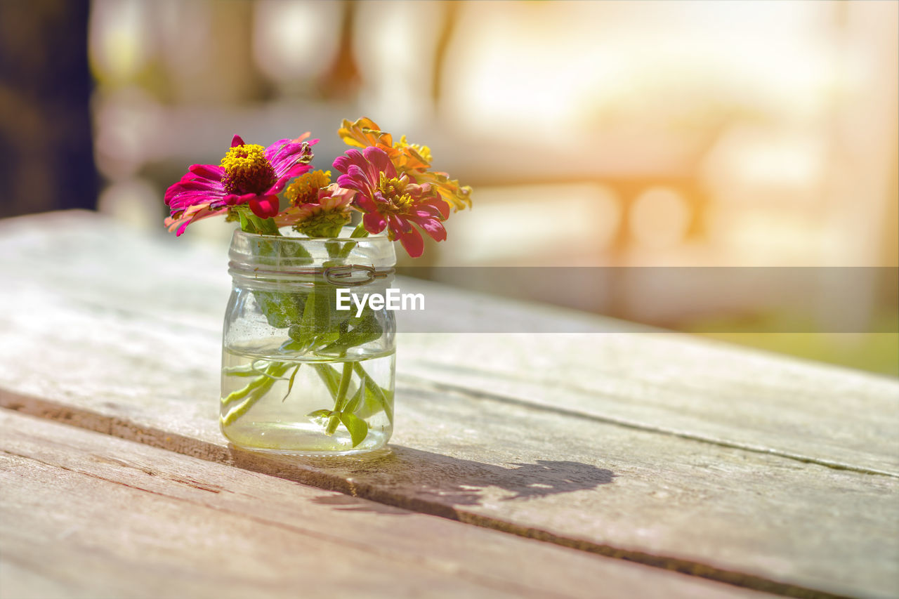 CLOSE-UP OF FLOWER VASE ON TABLE AT HOME