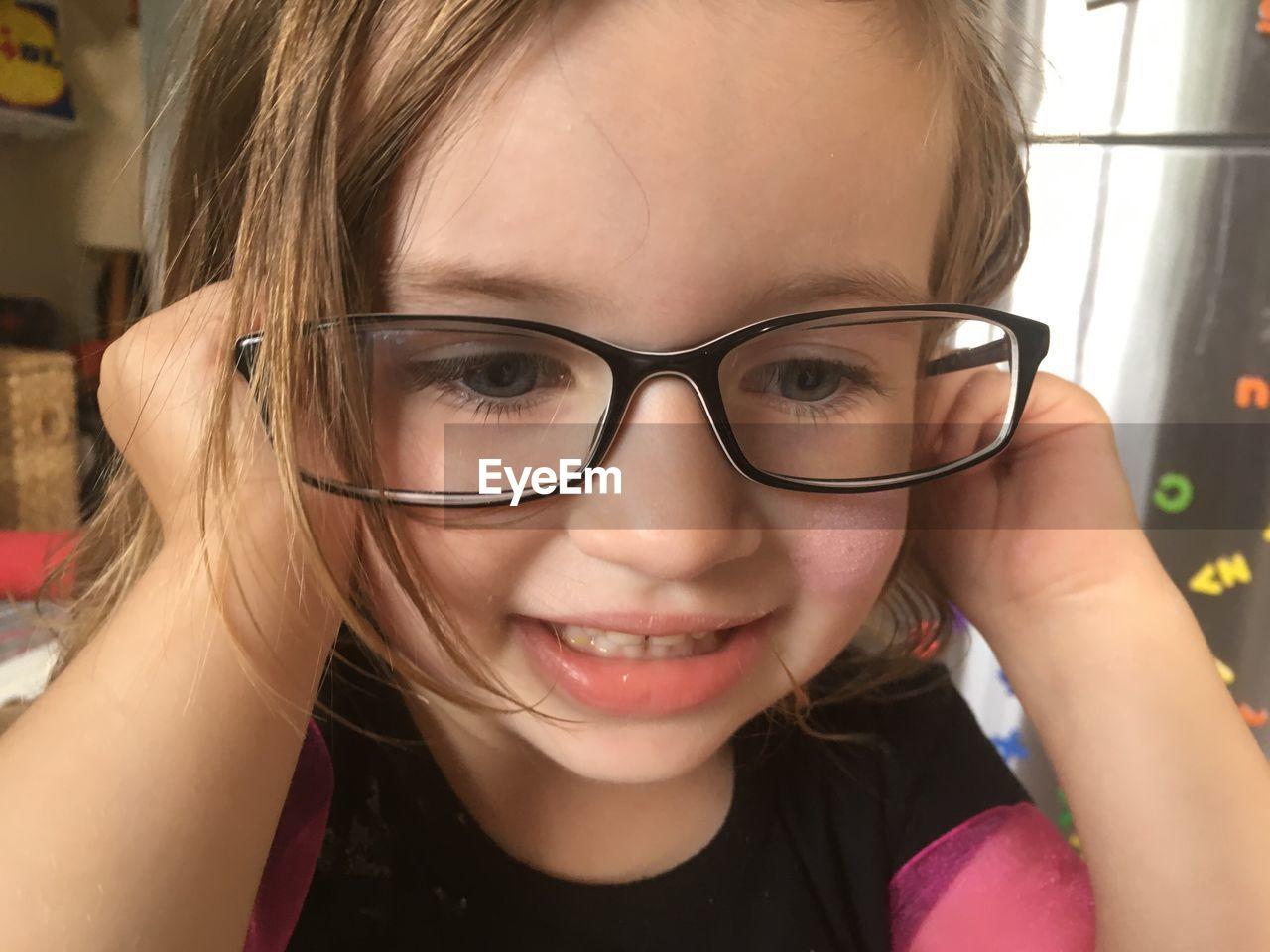 Close-up of smiling girl wearing eyeglasses looking away at home