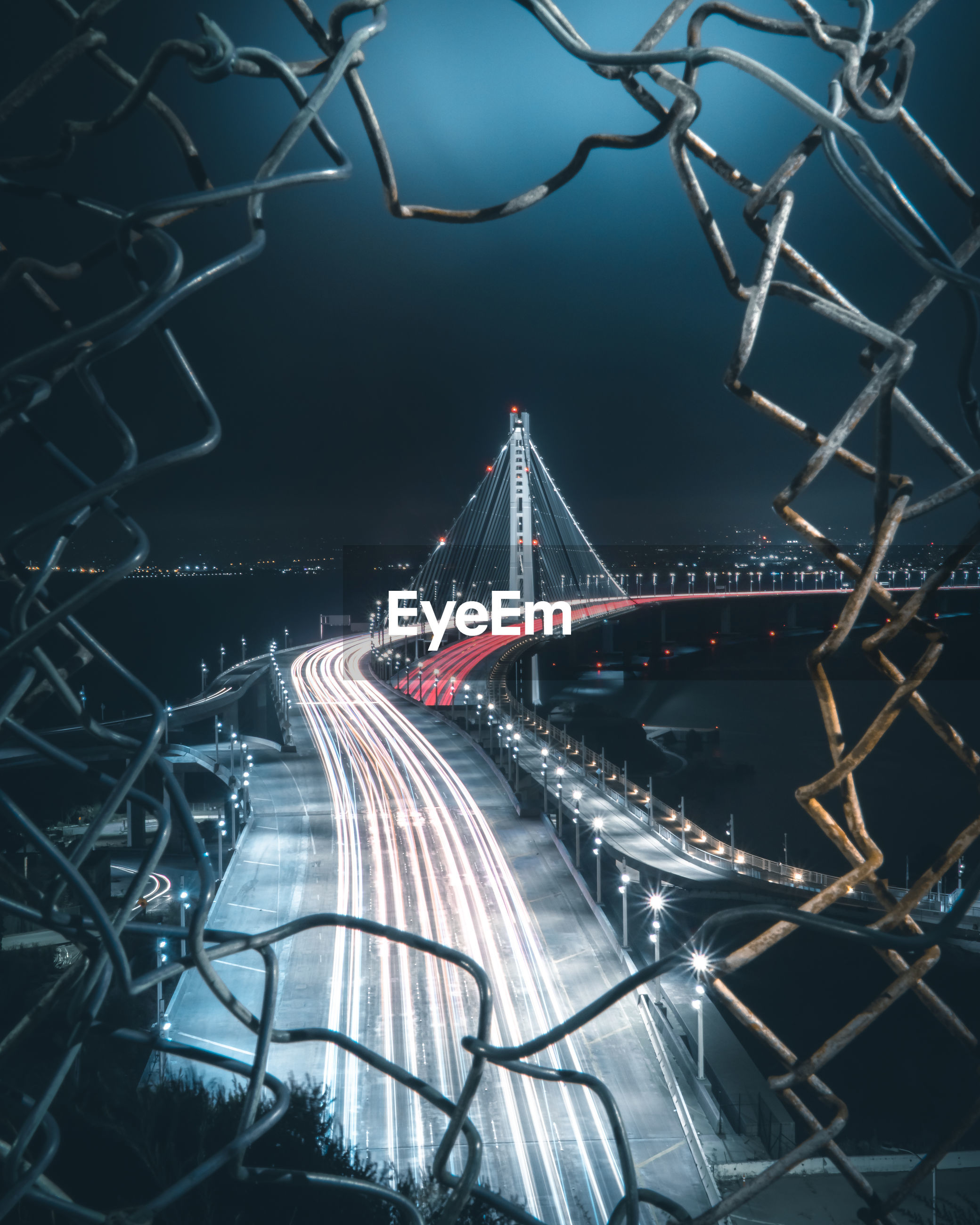 High angle view of light trails on bridge seen through hole in fence