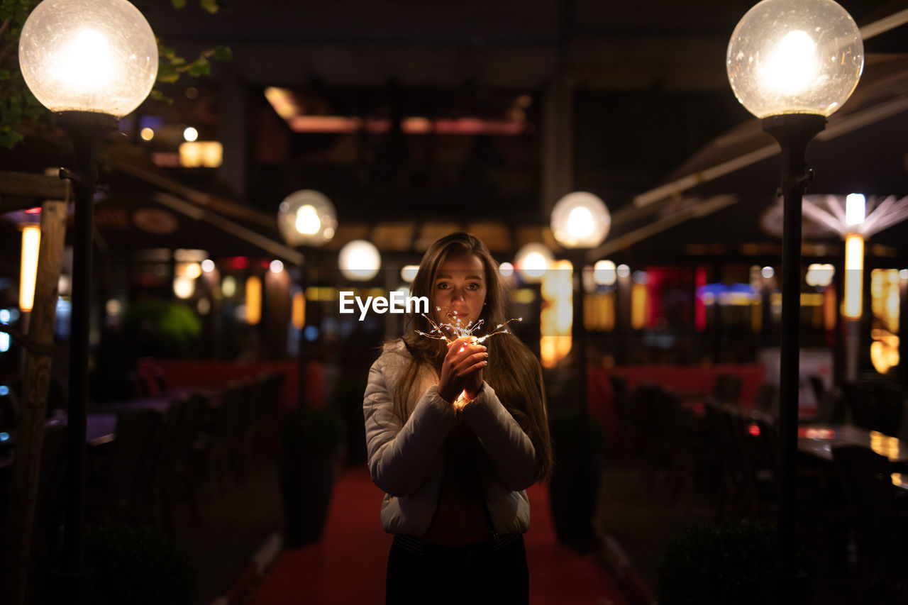 Young Woman Holding Illuminated Lighting Equipment While Standing At Entrance Of Restaurant