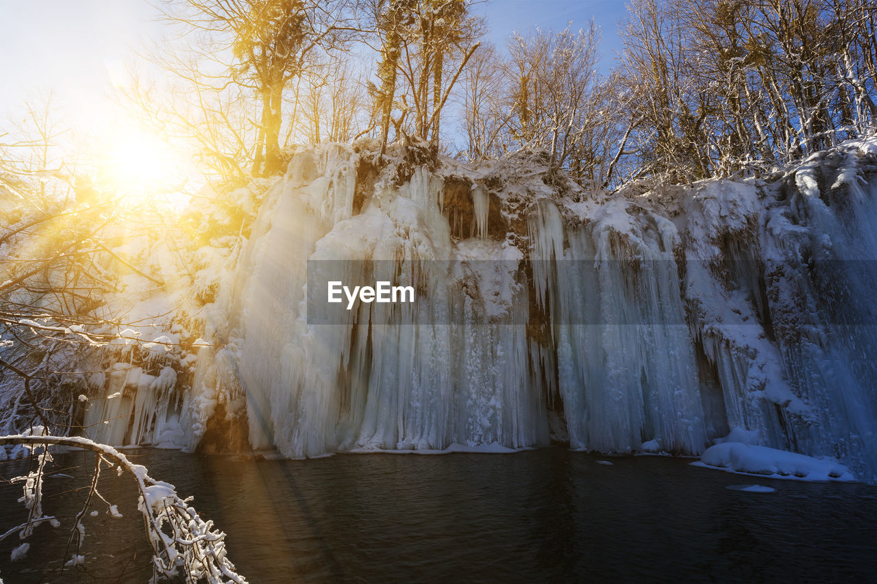water, beauty in nature, cold temperature, tree, ice, winter, frozen, nature, scenics - nature, sky, snow, icicle, tranquility, no people, environment, plant, tranquil scene, waterfront, outdoors, flowing water