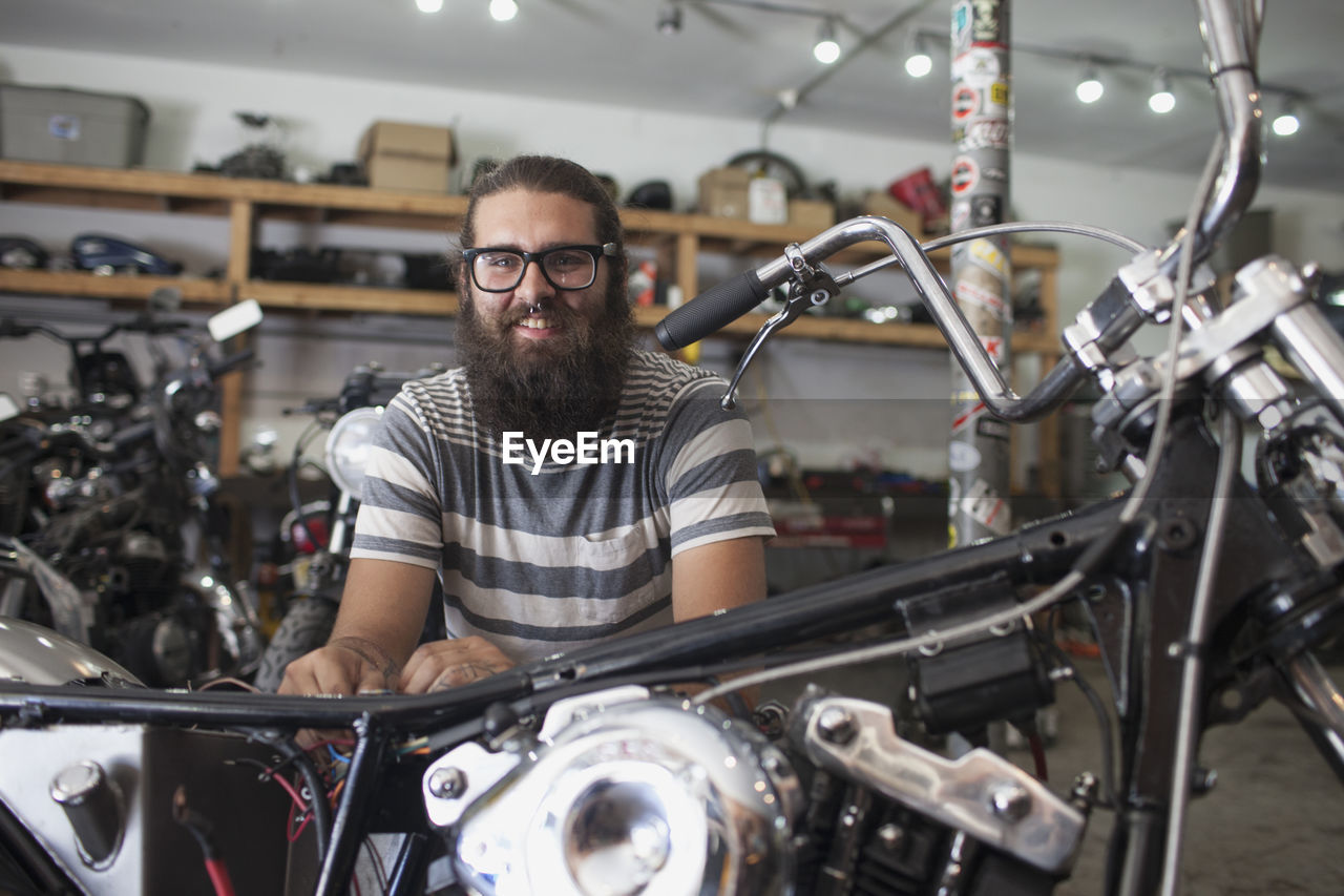 glasses, transportation, bicycle, one person, occupation, portrait, mid adult, front view, men, facial hair, adult, indoors, beard, small business, eyeglasses, mode of transportation, mid adult men, looking at camera, males, bicycle shop, entrepreneur, biker