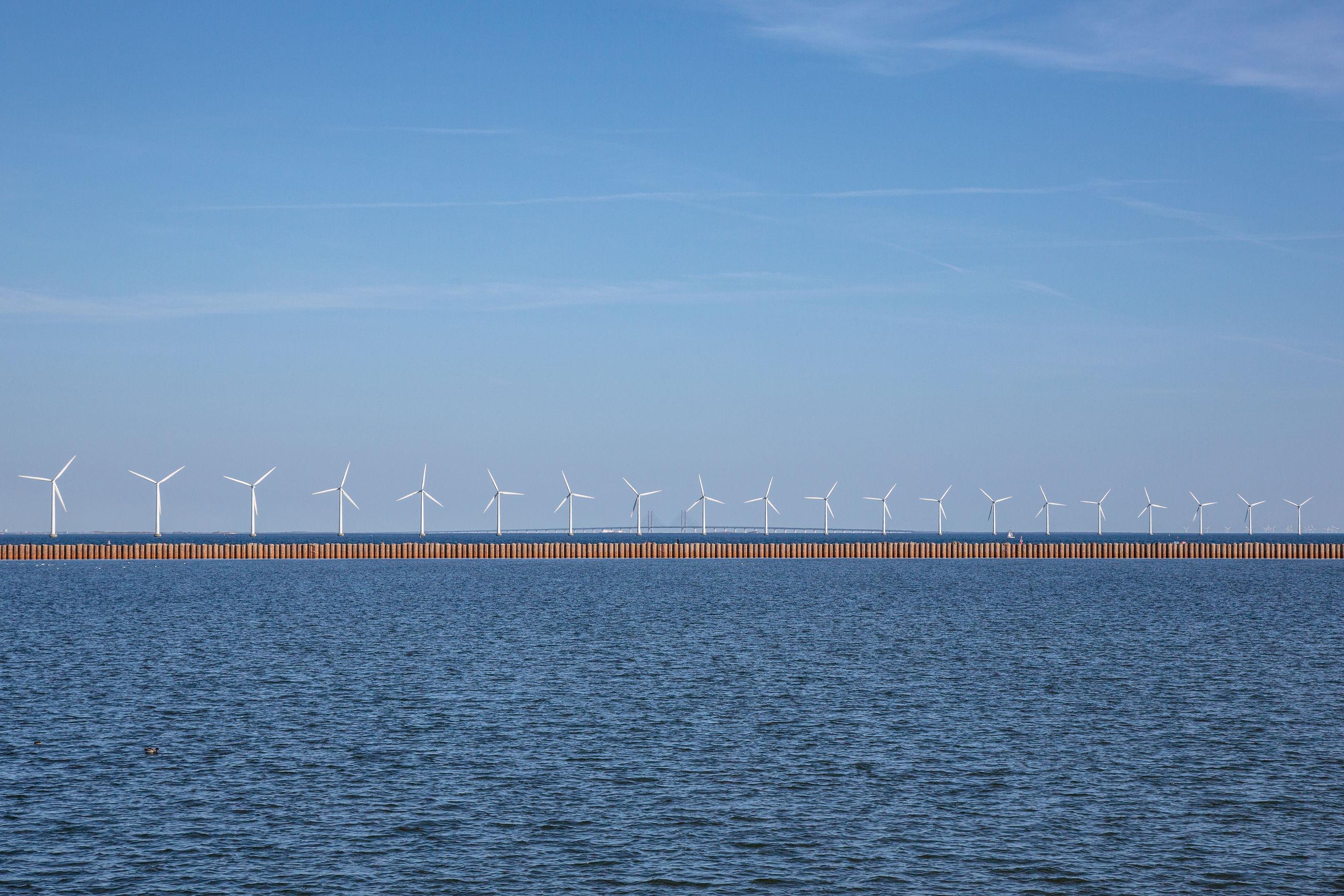 View of wind turbines on sea against blue sky