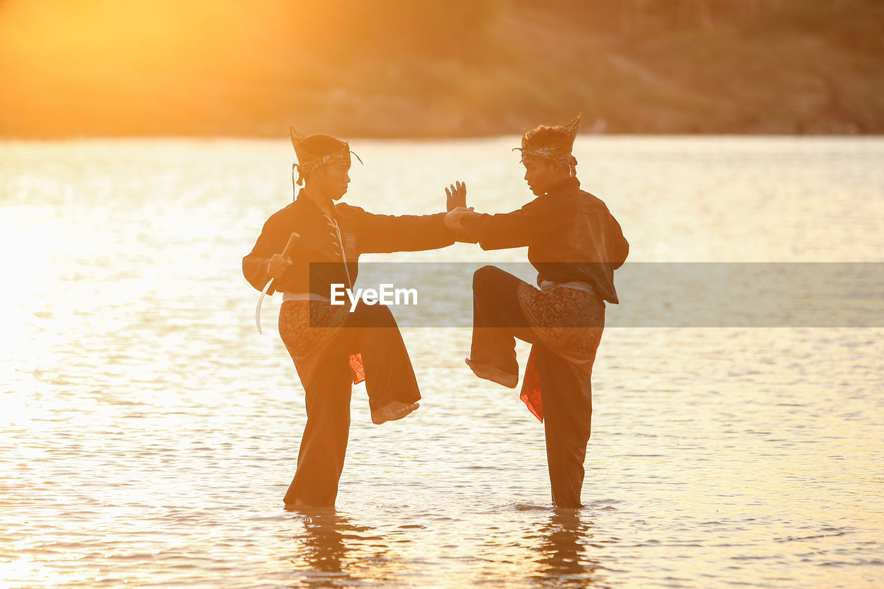 water, two people, sunset, togetherness, sky, sea, lifestyles, real people, leisure activity, beauty in nature, nature, sunlight, bonding, orange color, standing, adult, land, women, men, positive emotion, outdoors