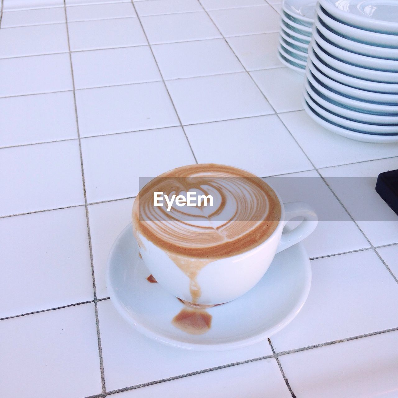 Close-Up Of Coffee Cup On Tiled Floor