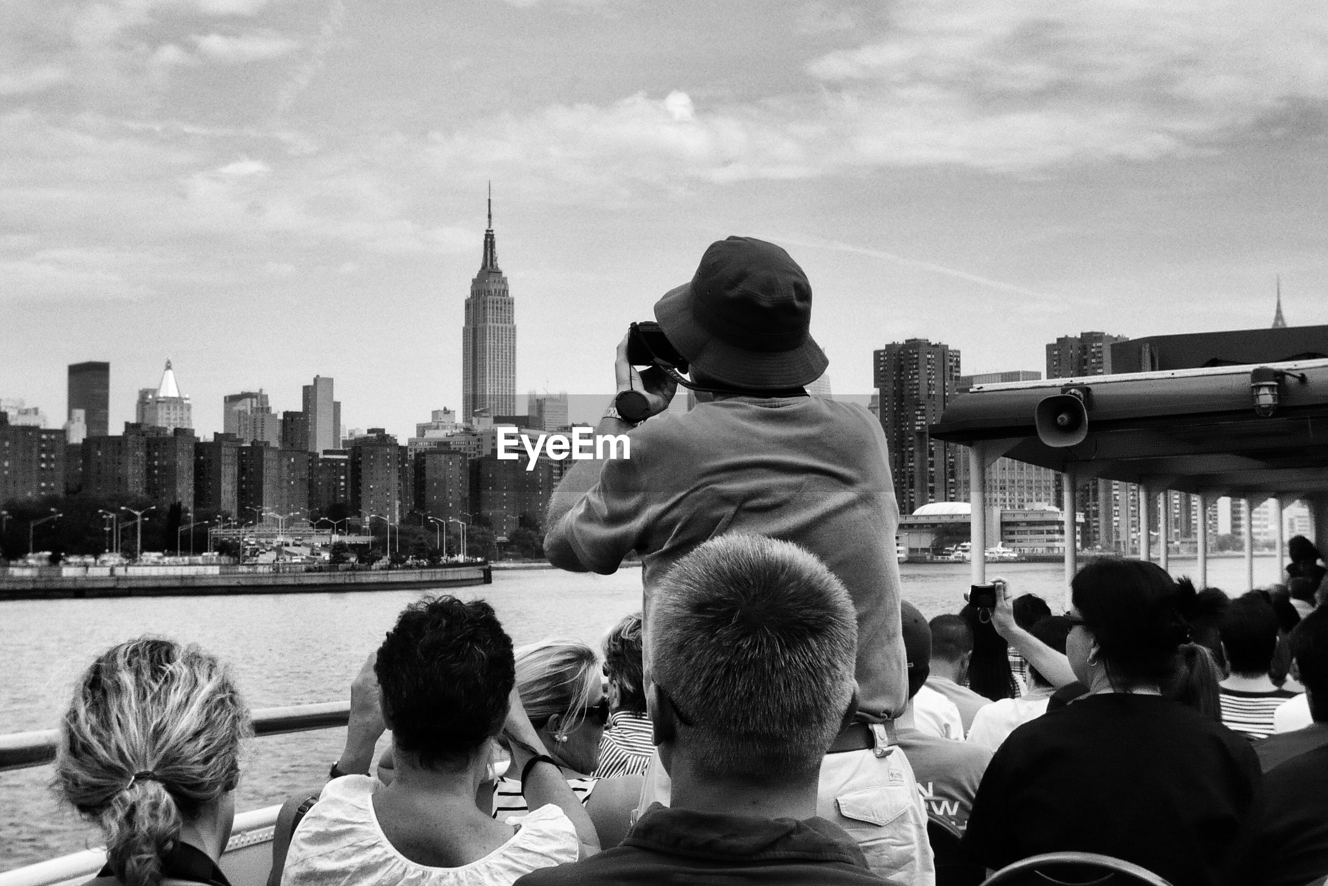 Tourist sailing on ferry by empire state building and city against sky
