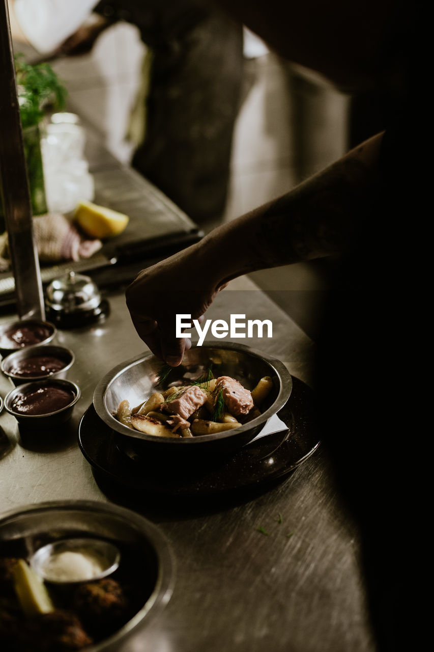 Hand garnishing food with rosemary in restaurant