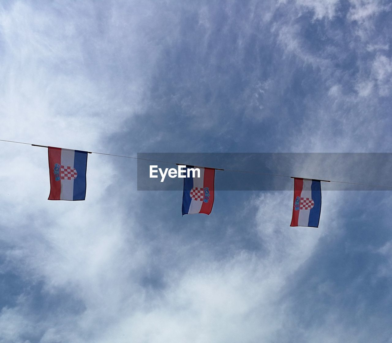 Low angle view of croatian flags waving on rope against sky