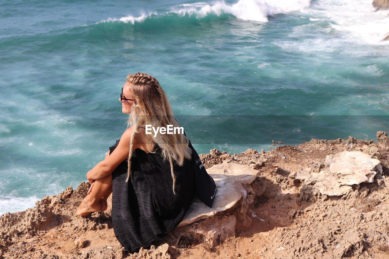 Woman sitting on rock at beach