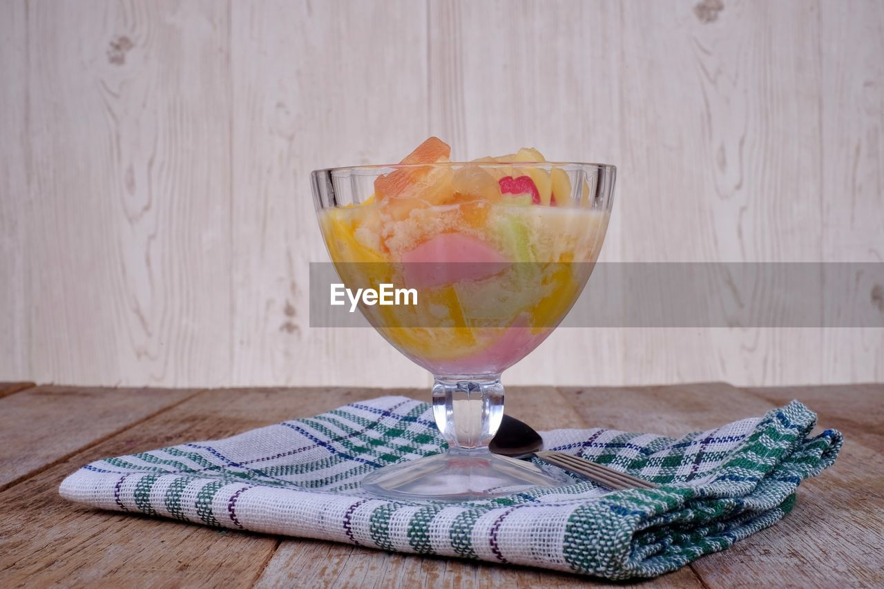 table, food and drink, glass, wood - material, still life, drink, refreshment, food, indoors, freshness, alcohol, no people, glass - material, drinking glass, household equipment, wineglass, close-up, napkin, transparent, fruit, cocktail