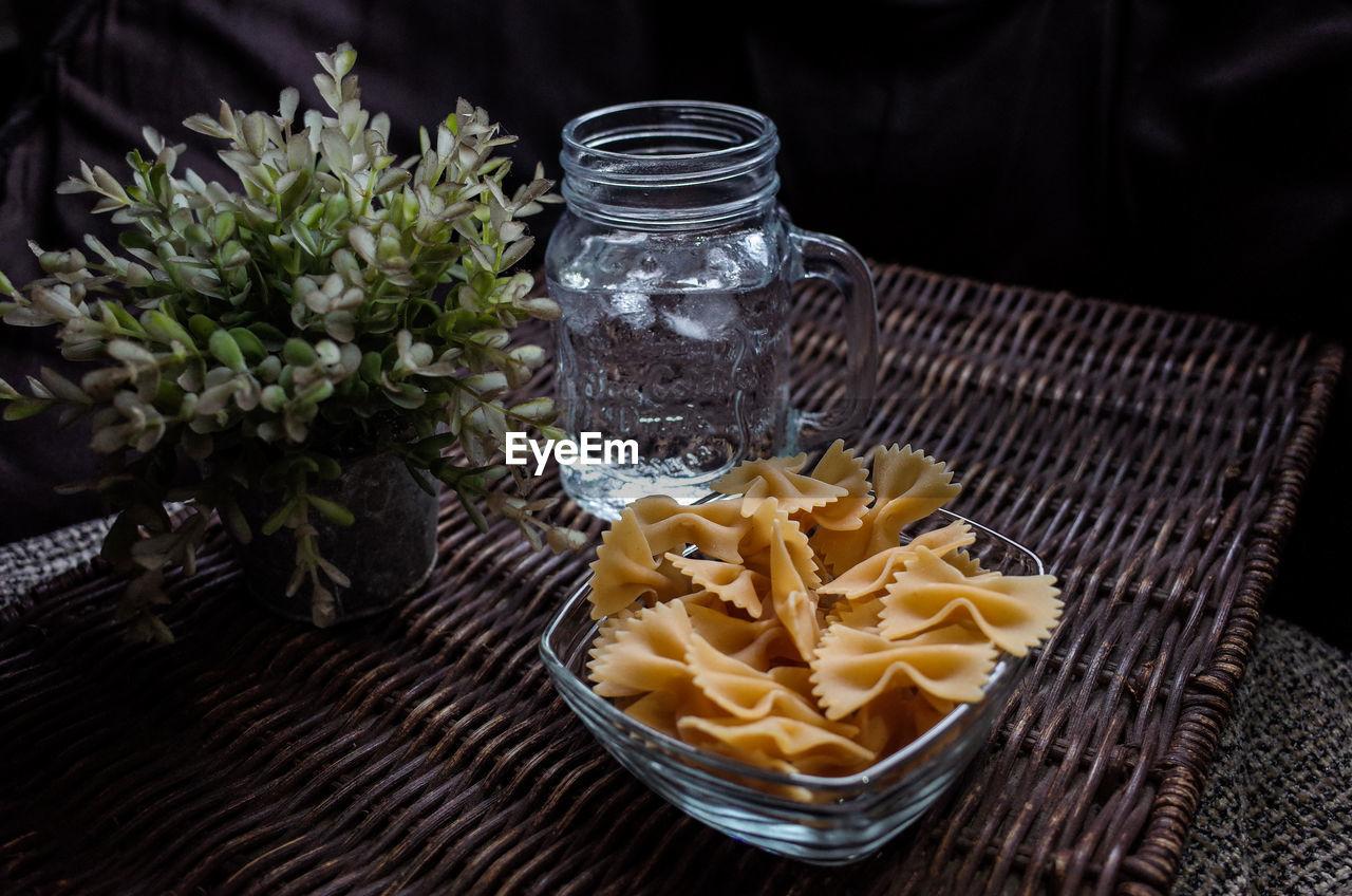 Farfalle Pasta And Drinking Water On Wicker Mat