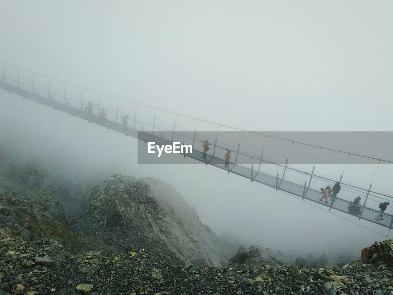 High angle view of people walking on footbridge in foggy weather