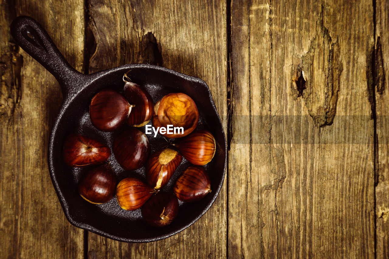 food and drink, wood - material, food, kitchen utensil, freshness, directly above, brown, healthy eating, table, spoon, close-up, indoors, wellbeing, no people, still life, household equipment, eating utensil, bowl, high angle view, chestnut - food, frying pan, wooden spoon, wood grain