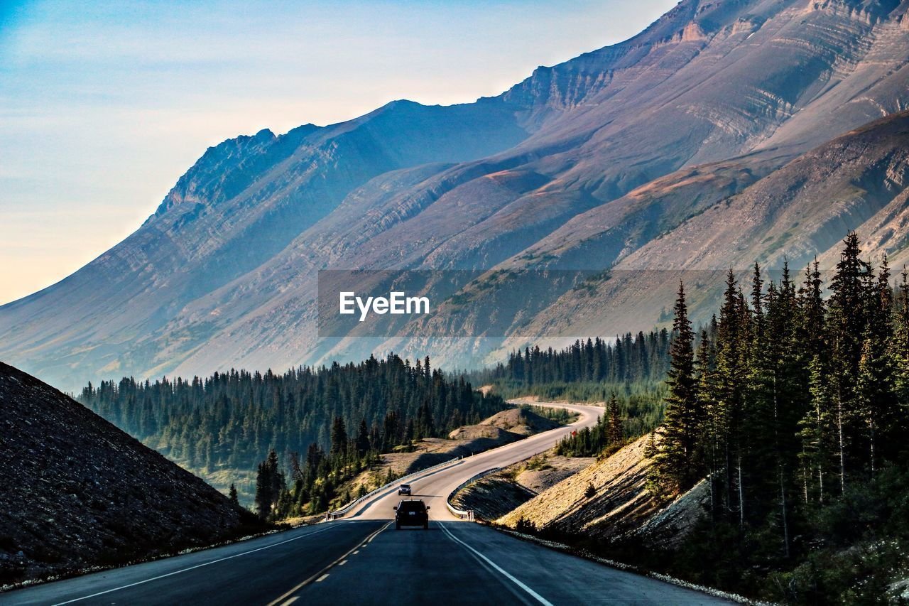 PANORAMIC VIEW OF ROAD BY MOUNTAINS AGAINST SKY