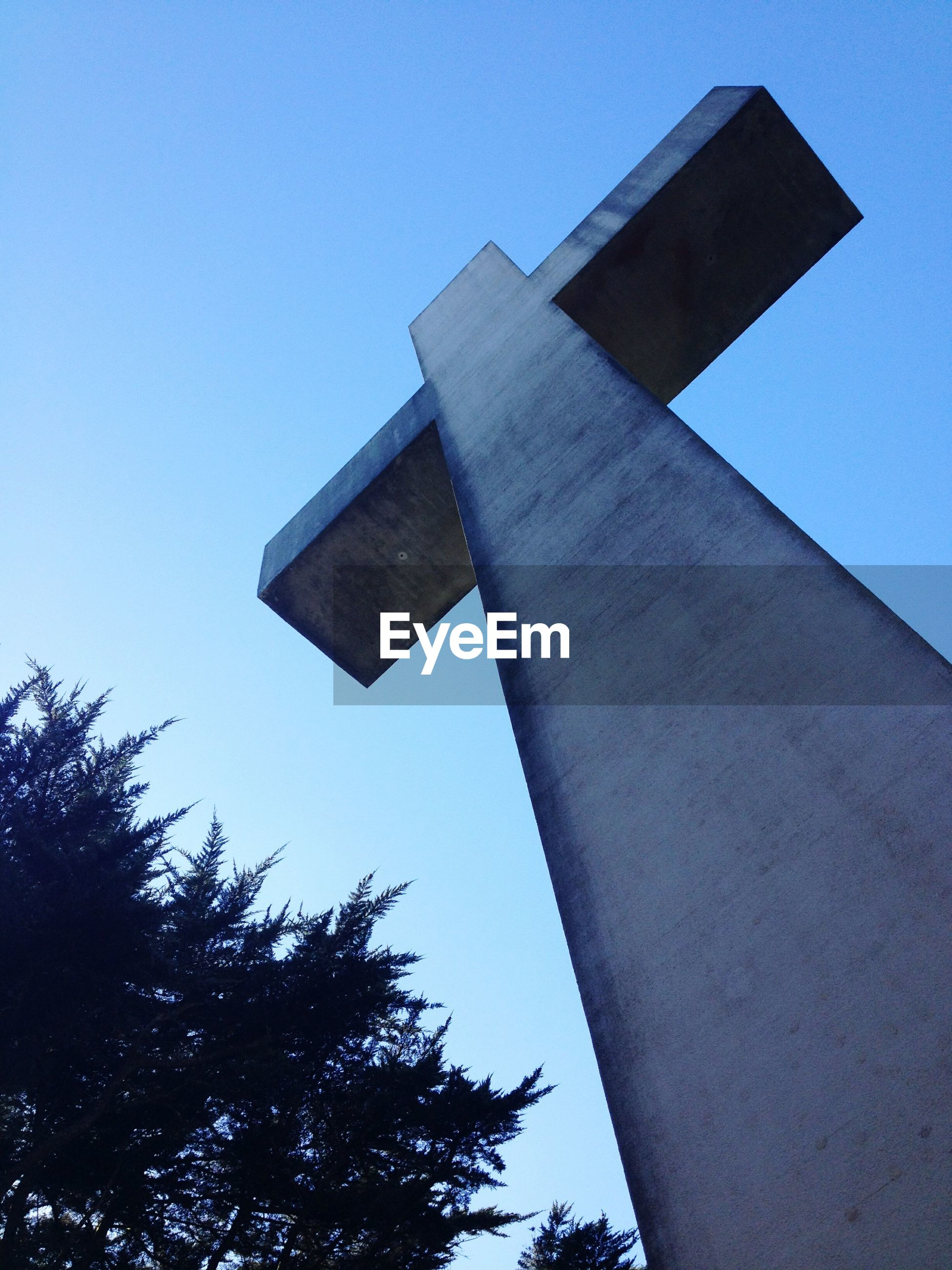 low angle view, architecture, clear sky, built structure, building exterior, tree, religion, blue, cross, tower, spirituality, place of worship, sky, copy space, day, church, no people, outdoors
