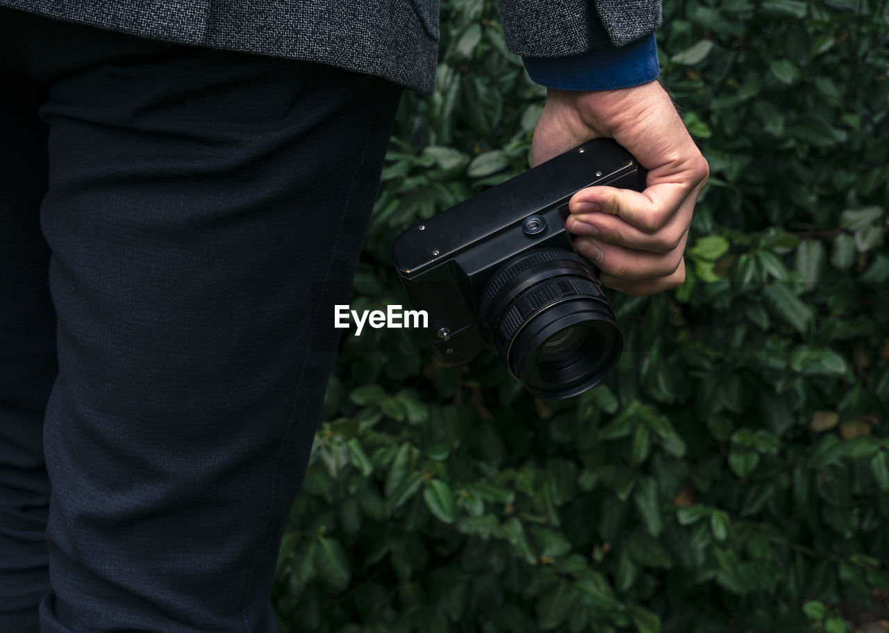 Midsection Of Man Holding Camera Against Plants