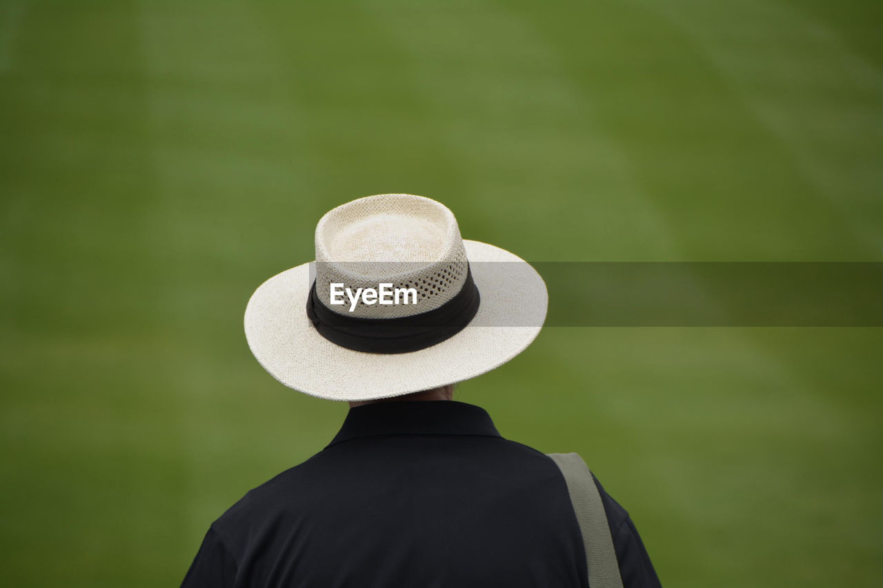 Rear View Of Man Wearing Straw Hat On Field