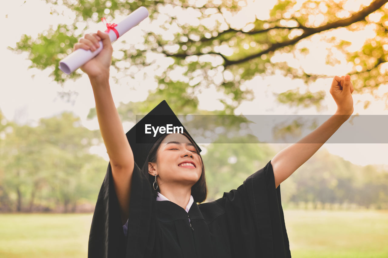 Young woman in graduation gown with arms raised holding certificate while standing at park