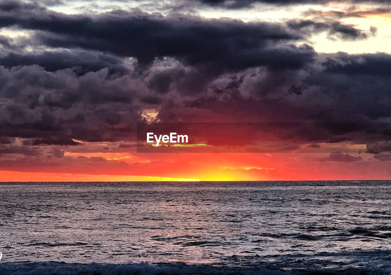 sunset, beauty in nature, sea, scenics, tranquility, tranquil scene, cloud - sky, nature, sky, dramatic sky, orange color, idyllic, no people, water, horizon over water, sun, outdoors, awe, storm cloud, day