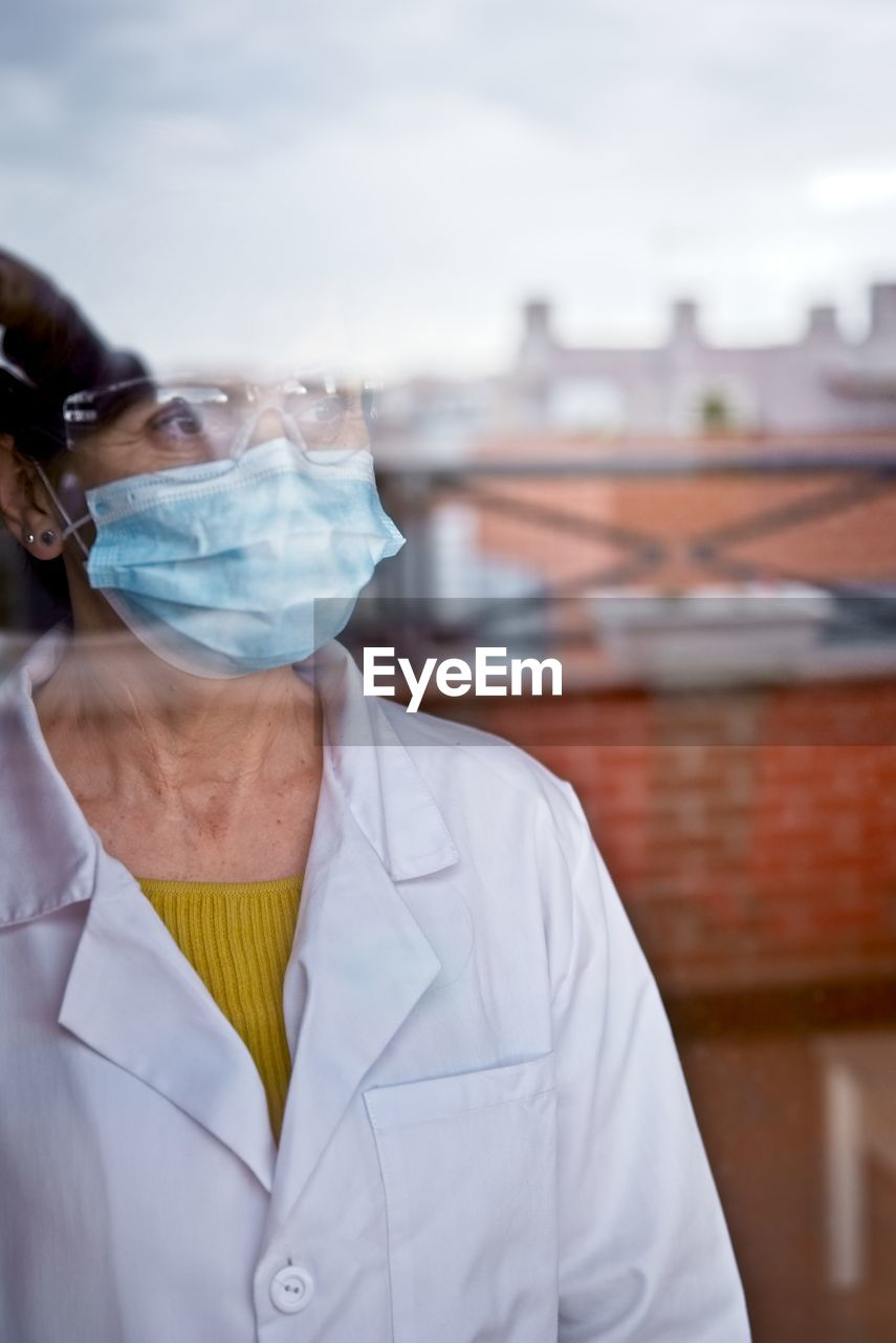A woman in a white coat looks through the window