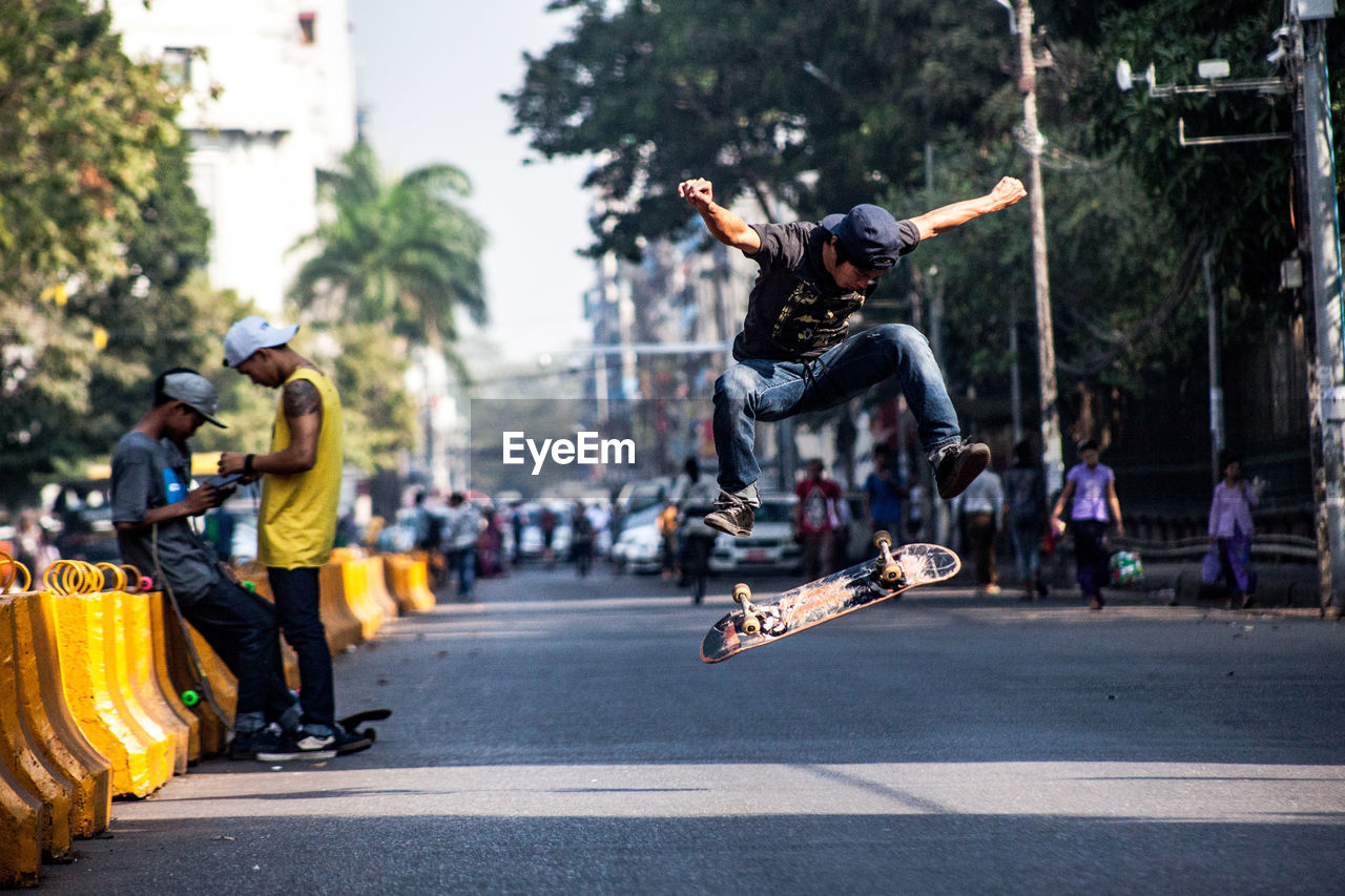 Young Man Skateboarding On Road In City