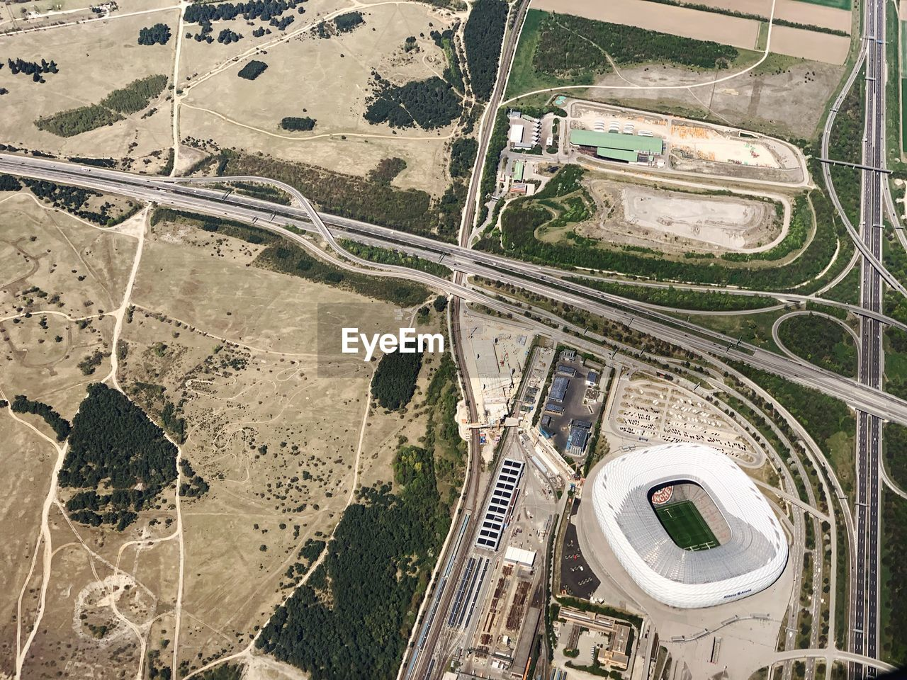aerial view, high angle view, transportation, road, day, built structure, nature, architecture, no people, outdoors, travel, airplane, air vehicle, landscape, mode of transportation, city, environment, connection, building exterior, flying, multiple lane highway, overpass