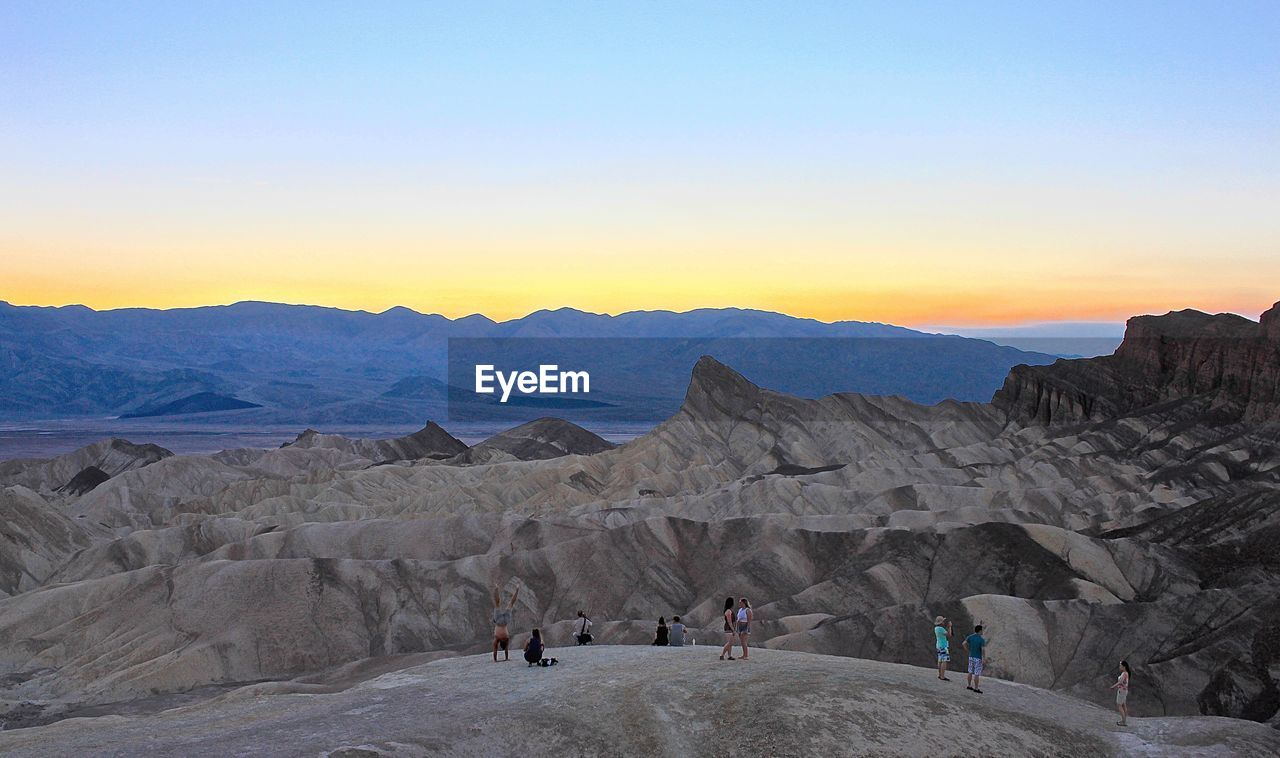 Tourists At Zabriskie Point Against Clear Sky During Sunset