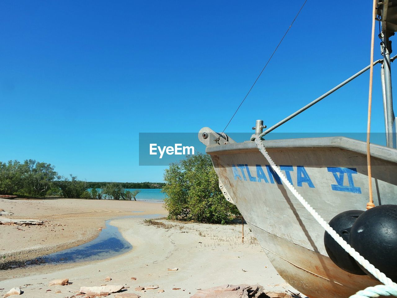 Cropped image of boat moored at shore against clear sky