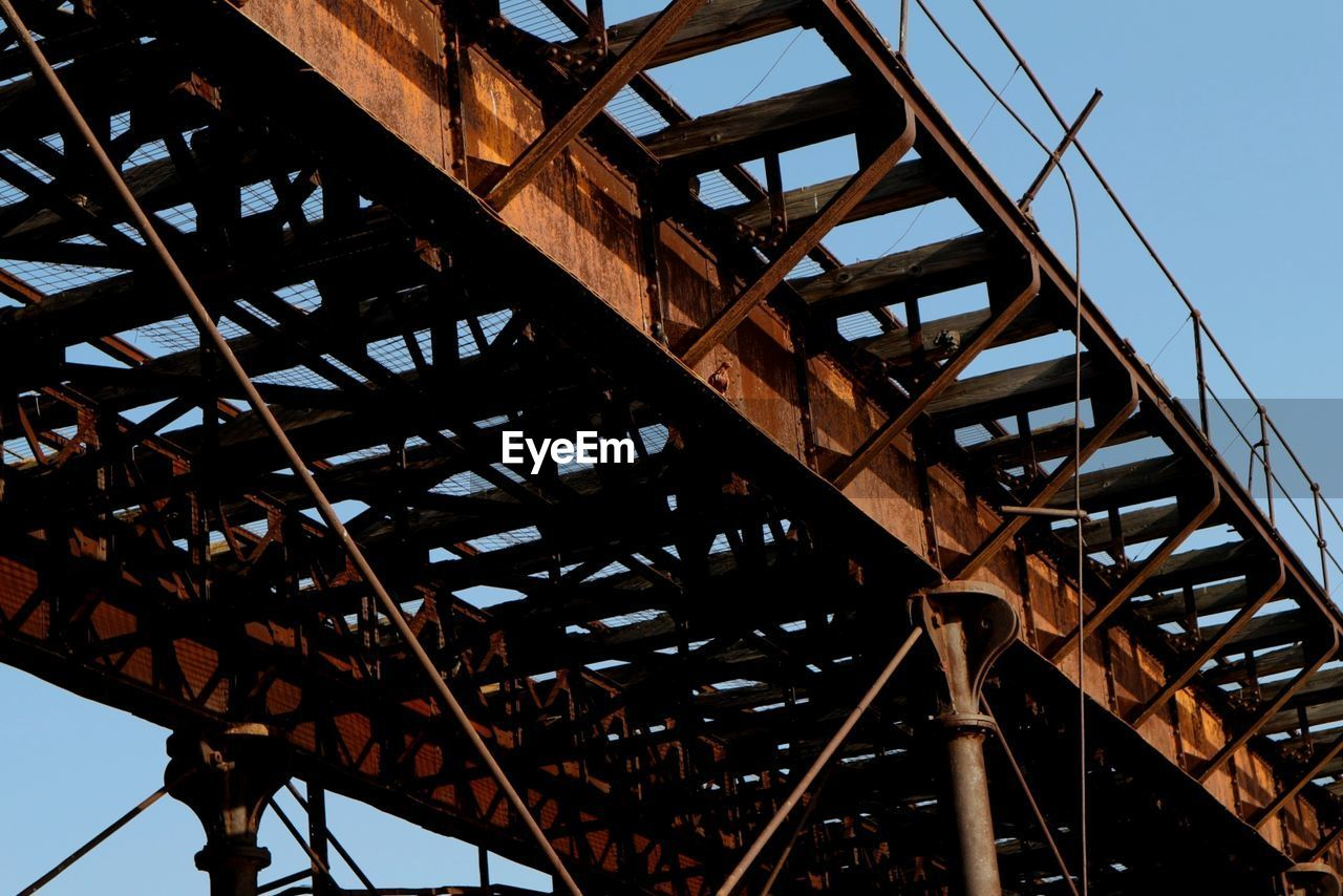 low angle view, architecture, sky, built structure, metal, no people, nature, day, clear sky, connection, outdoors, bridge, bridge - man made structure, industry, transportation, rusty, tower, old, close-up, girder