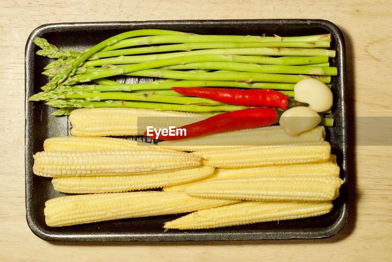 High angle view of vegetables in tray on wooden table