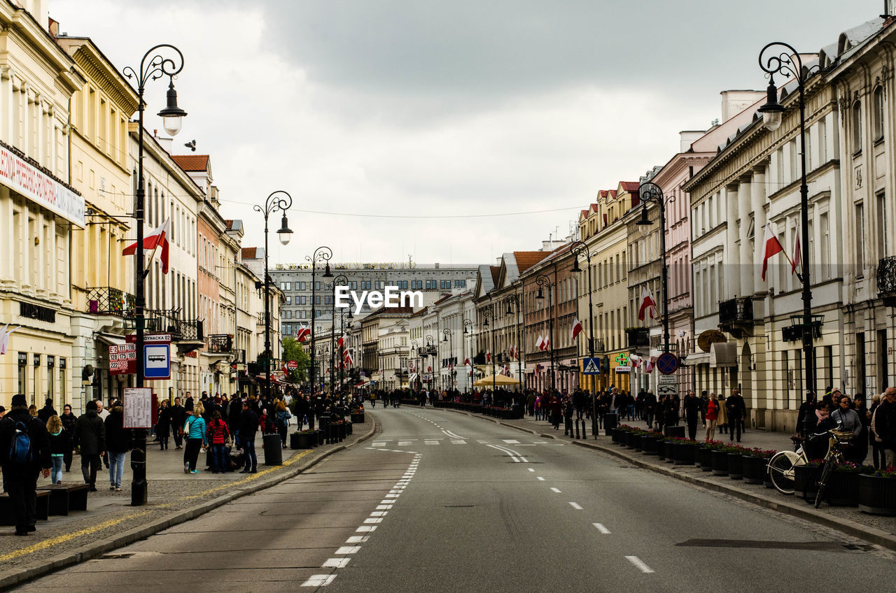 building exterior, built structure, architecture, road marking, sky, road, street, large group of people, day, the way forward, outdoors, cloud - sky, city, people