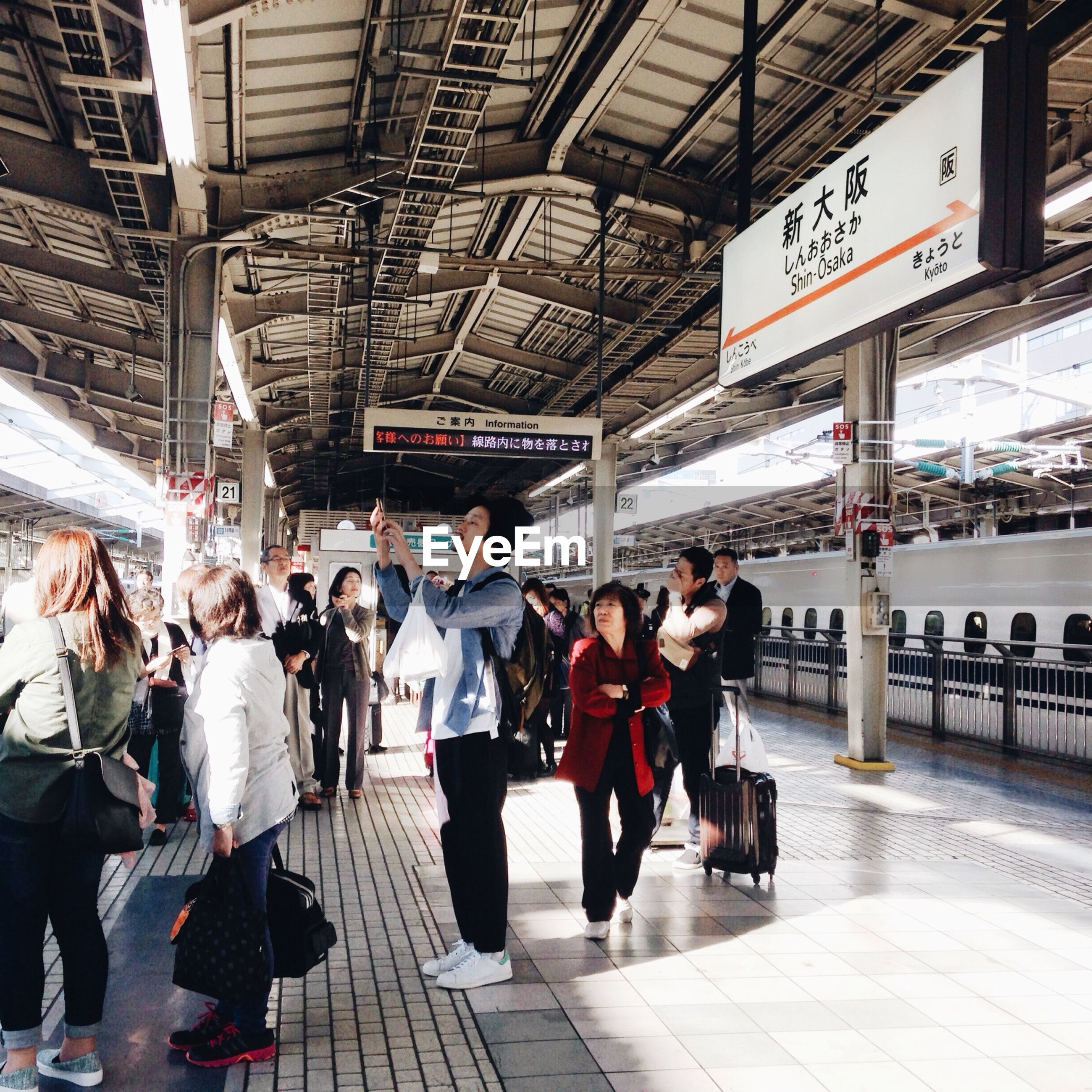 large group of people, men, person, lifestyles, railroad station, indoors, architecture, built structure, walking, city life, leisure activity, public transportation, subway station, text, travel, transportation, railroad station platform, communication, city