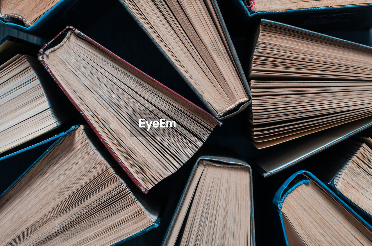 Parted books next to each other top view. background from multicolored old books.