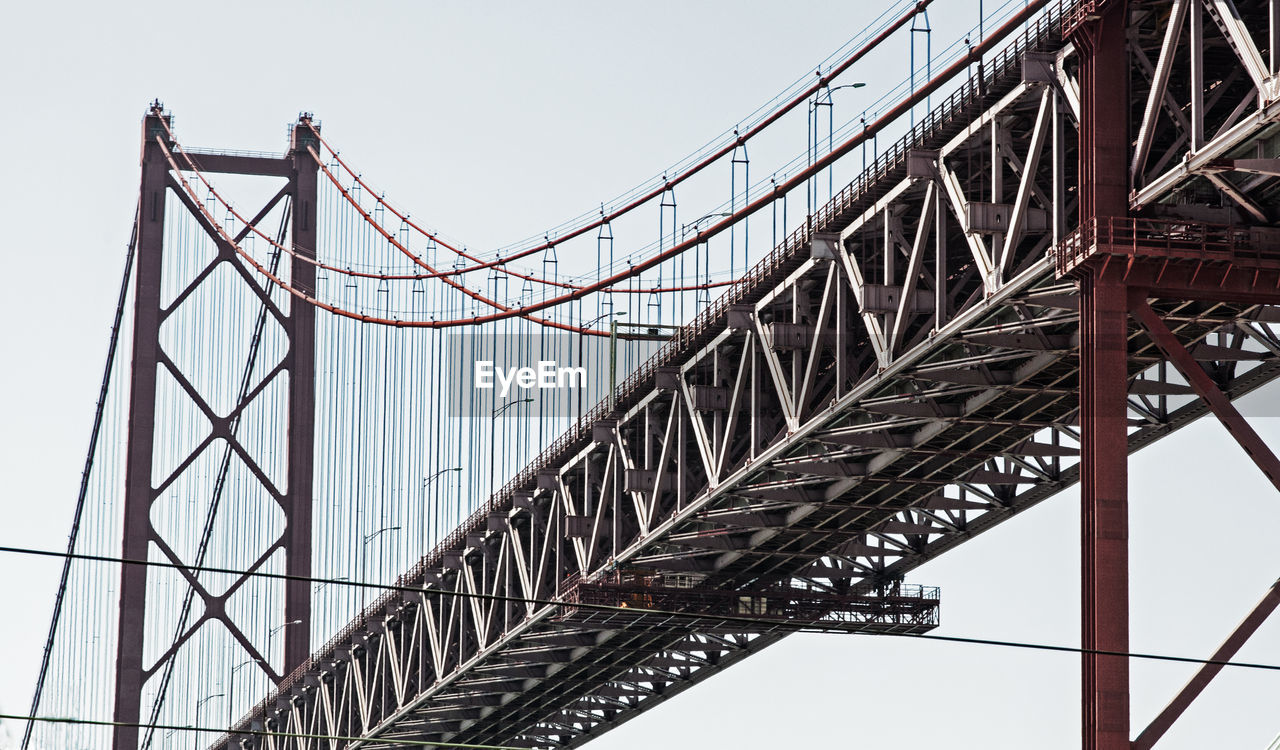 LOW ANGLE VIEW OF SUSPENSION BRIDGE CABLES AGAINST SKY