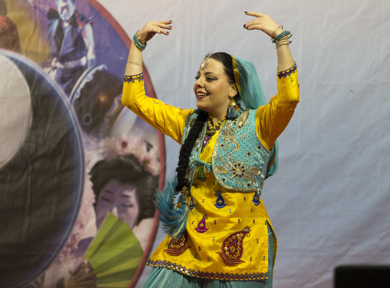 traditional clothing, young women, arms raised, young adult, happiness, real people, lifestyles, smiling, leisure activity, yellow, enjoyment, dancing, casual clothing, front view, fun, celebration, holding, traditional festival, standing, beautiful woman, sari, day, outdoors, togetherness, adult, people