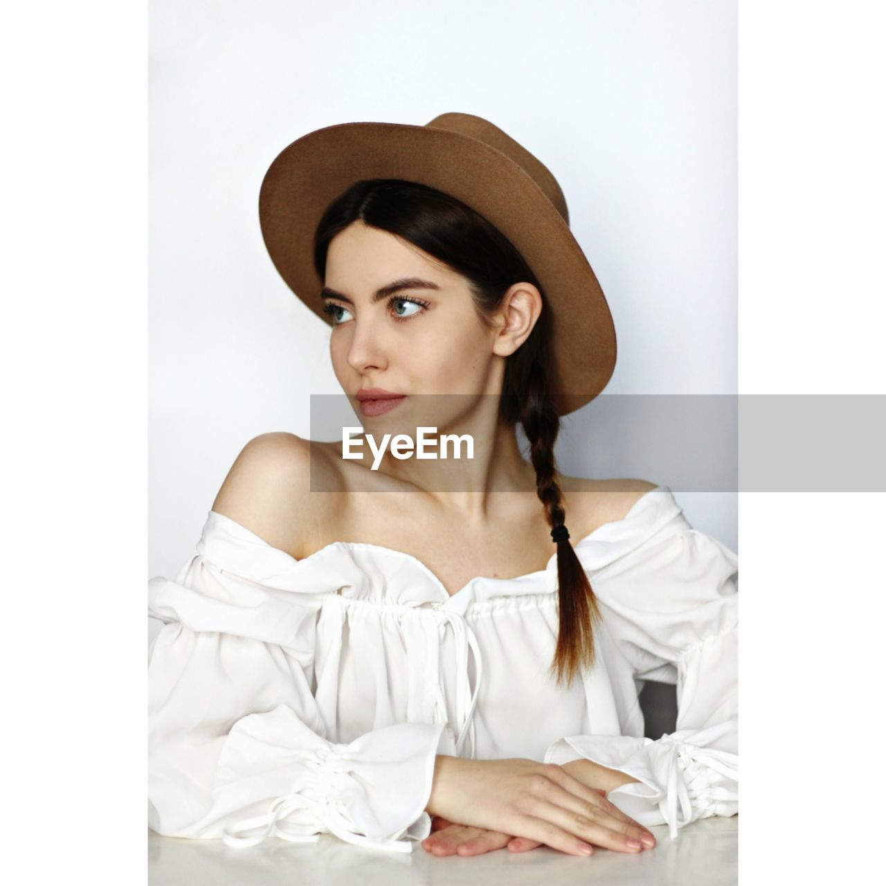Beautiful young woman looking away while wearing hat at home
