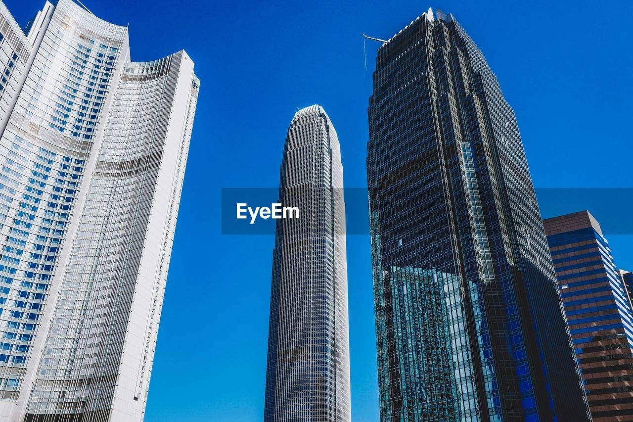 building exterior, architecture, built structure, office building exterior, building, city, skyscraper, tall - high, modern, low angle view, sky, office, tower, no people, clear sky, blue, nature, day, glass - material, urban skyline, outdoors, financial district
