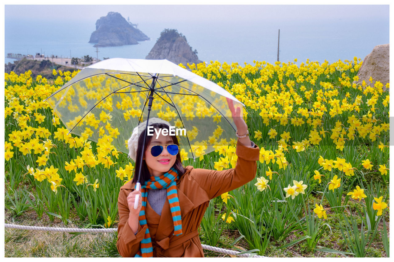 Smiling woman holding umbrella against yellow flowering plants