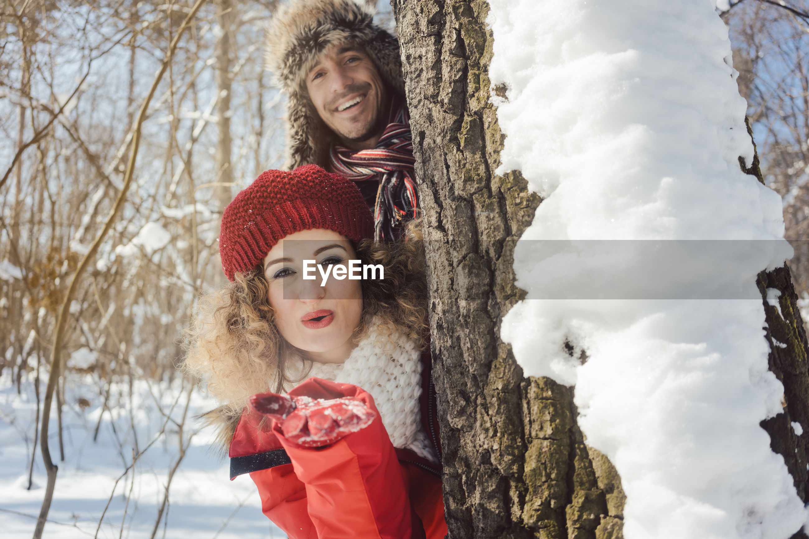 Portrait of smiling couple peeking through tree trunk in forest during winter